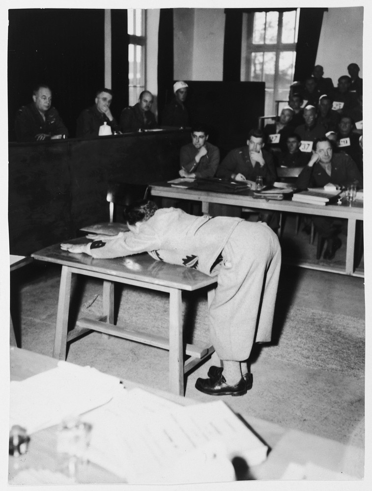 A prosecution witness demonstrates the position prisoners were forced to assume for punishment on the whipping block in the Dachau ... [LCID: 61085]