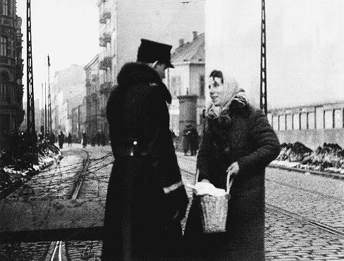A Polish policeman searches the bag of a Jewish resident of the ghetto. [LCID: 5433]