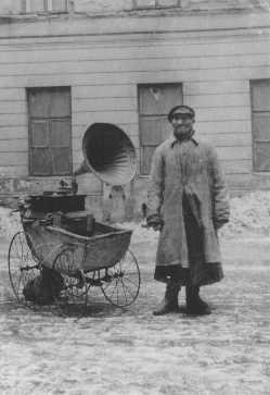 A Jewish man attempts to make a living by playing music on a gramophone, which he wheels around in an old baby carriage. [LCID: 66813]