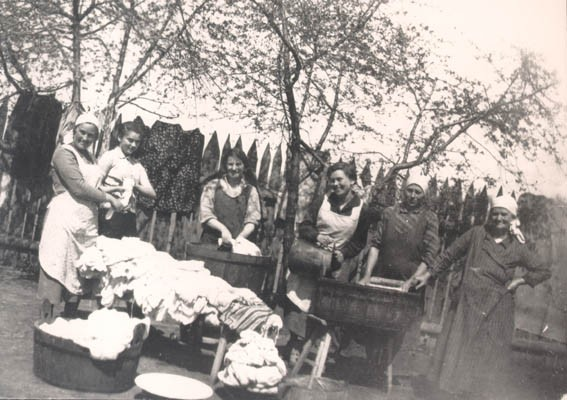 Four of Norman's sisters, the maid, and Norman's mother, Esther, do laundry in the yard of their home.