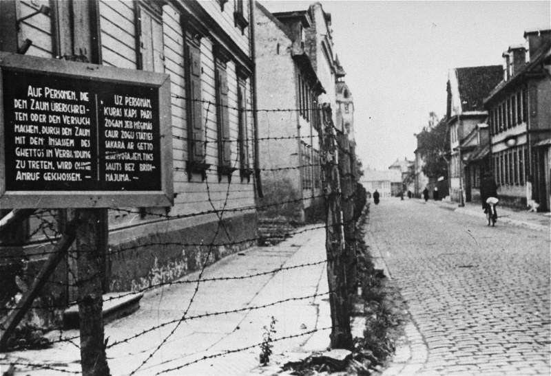 <p>Tábla német és lett felirattal, amely arra figyelmeztet, hogy a kerítést átlépő vagy a rigai gettó lakóival kapcsolatot létesítő személyeket lelövik. Riga, Lettország, 1941–1943.</p>