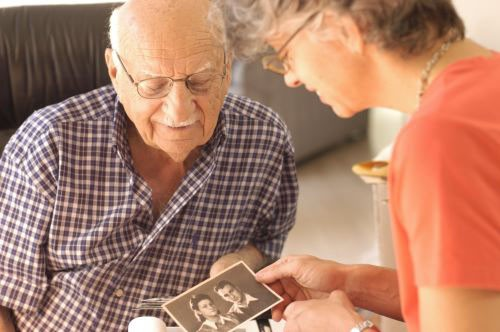 <p>Aron Derman and Neenah Ellis look at one of Aron's family photographs. 2004.</p>