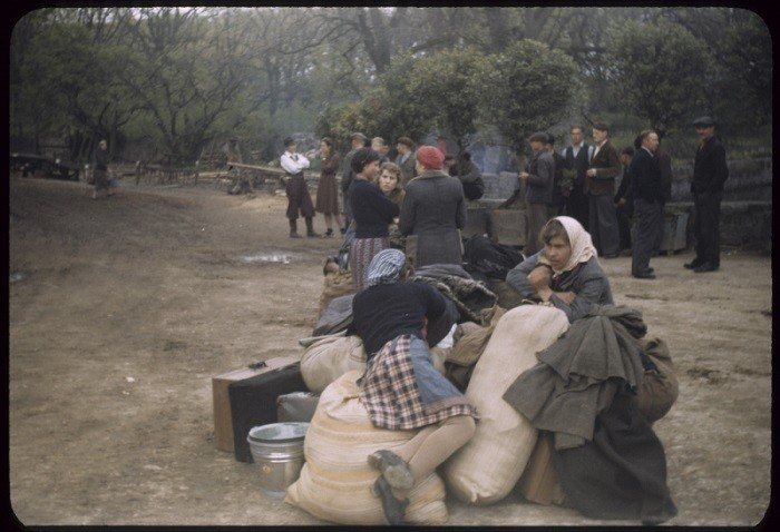 <p>Displaced persons wait next to their suitcases and bundles, place uncertain, ca. 1947.</p>