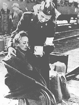 <p>A Red Cross official gives assistance to a former concentration camp prisoner who was transported to Sweden under an agreement with the Swedish Red Cross. Malmo, Sweden, April 1945. [Please contact Beth Hatefutsoth for copies of this photograph.]</p>