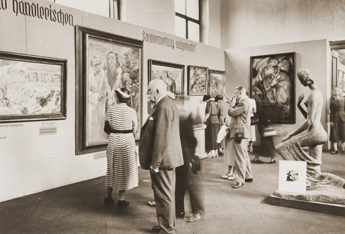 "<p>Visitors view the <a href=""/narrative/60322"">""Degenerate Art""</a> exhibition (<em>Entartete Kunst</em>) at the Munich Hofgarten in July 1937. Works by Lovis Corinth and Franz Marc are visible, among others.</p>"