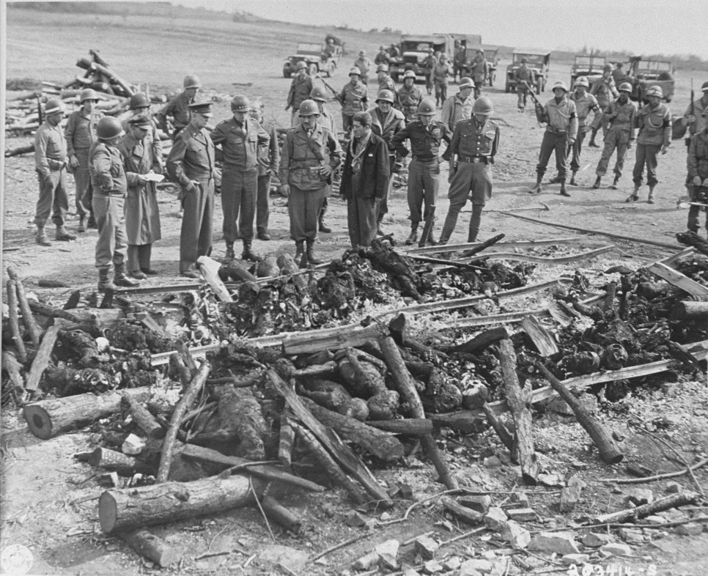 """<p>General Dwight D. Eisenhower (third from left) views the charred remains of inmates of the <a href=""""/narrative/7757/en"""">Ohrdruf</a> camp. Ohrdruf, Germany, April 12, 1945.</p>"""
