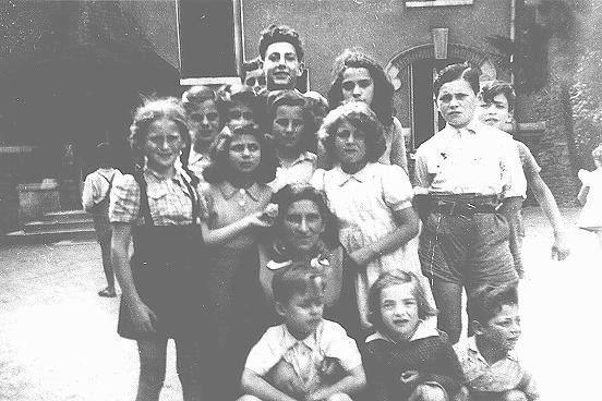 <p>A group of children surrounding Hermine Markovitz at the Children's Aid Society (Oeuvre de Secours anx Enfants; OSE) home for children in Draveil. France, postwar.</p>