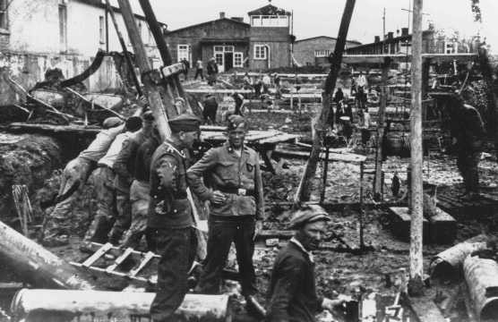 """<p>SS men supervise laborers at construction work. <a href=""""/narrative/6811"""">Neuengamme</a> concentration camp, Germany, winter 1943.</p>"""