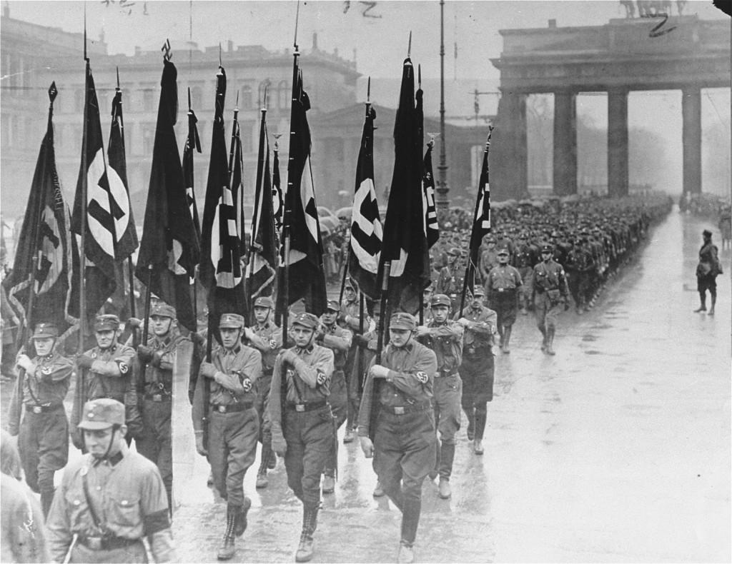 <p>Membros das Tropas de Choque (SA) marcham sob o portão de Brandenburg. Berlim, Alemanha. 8 de abril de 1933.</p>