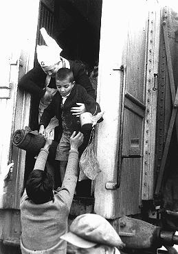 """<p>A nurse helps one of the """"<a href=""""/narrative/11006/en"""">Tehran Children</a>,"""" Polish Jewish refugees, disembark from a train at the Atlit refugee camp. Atlit, Palestine, February 18, 1943.</p>"""