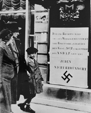 Viennese pedestrians view a large Nazi sign posted on a restaurant window informing the public that this business is run by an organization ... [LCID: 73943]