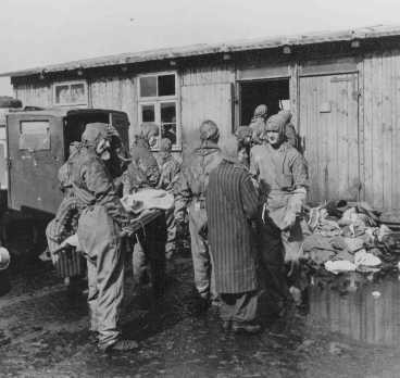 Soon after liberation, British medical officers begin disinfection of camp survivors. [LCID: 75116]