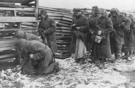 <p>Soviet prisoners of war pause for rations during forced labor at the narrow-gauge railroad station. Mlawa, Poland, about 1943.</p>