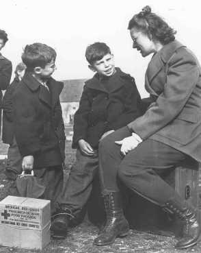 <p>Enfants juifs réfugiés de Budapest parlant à un employé de l'UNRRA (Administration des Nations Unies pour les secours et la reconstruction). Allemagne, après mai 1945.</p>