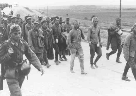 German soldiers guard Soviet prisoners of war marching to camps. [LCID: 91085]