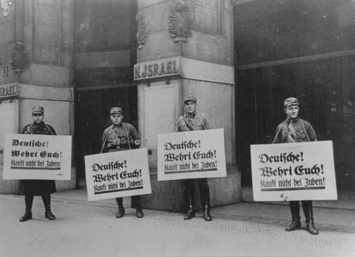 "SA men in front of Jewish-owned store urge a boycott with the signs reading ""Germans! [LCID: 66300b]"