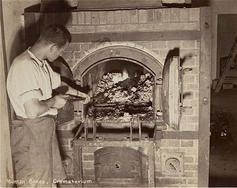 A survivor stokes smoldering human remains in a crematorium oven that is still lit. [LCID: 00315]