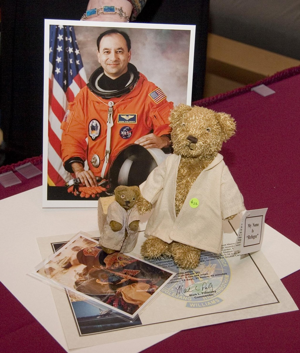 """<p>A replica of """"Refugee"""" bear and a photo of a Darfurian child refugee, items taken by Commander Mark Polansky (pictured) on a December 2006 Space Shuttle mission.</p>"""