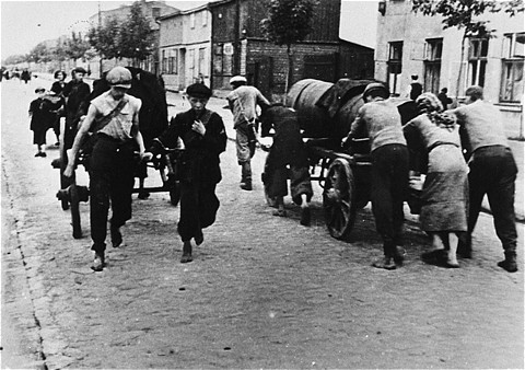 <p>Jews at forced labor, transporting excrement down a ghetto street. Lodz ghetto, Poland, wartime.</p>