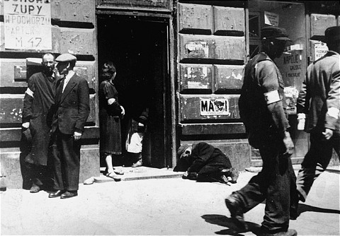 """Street scene in the Warsaw ghetto. The sign at left announces: """"Soup in the courtyard, first floor, apt. [LCID: 08292]"""