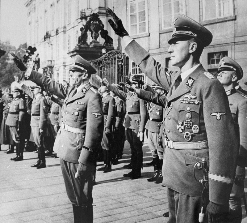 "<p><a href=""/narrative/10812"">Reinhard Heydrich</a> (right) and his deputy, Karl Hermann Frank (center), stand at attention during Heydrich's inauguration as governor of the Protectorate of <a href=""/narrative/10723"">Bohemia and Moravia</a>. Prague, September 1941.</p>"