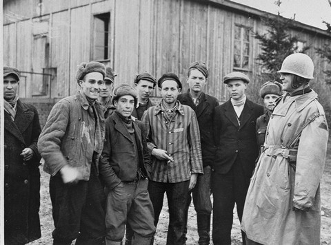 """<p>A US army officer (far right) poses with survivors of the <a href=""""/narrative/7757/en"""">Ohrdruf</a> camp, a subcamp in the <a href=""""/narrative/3956/en"""">Buchenwald</a> camp system. Photograph taken after the <a href=""""/narrative/2317/en"""">liberation</a> of the camp. Ohrdruf, Germany, April 1945.</p>"""