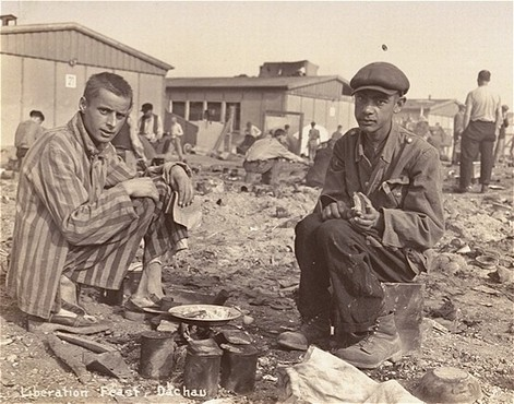 Two survivors prepare food outside the barracks. The man on the right, presumably, is Jean (Johnny) Voste, born in Belgian Congo, ... [LCID: 74095]
