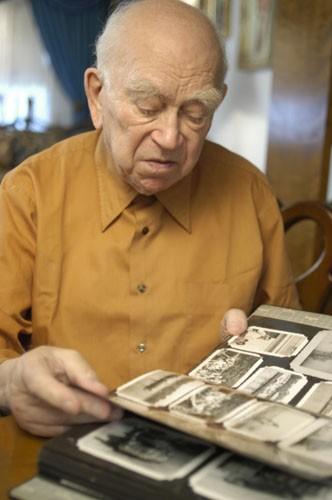 Norman Salsitz looks through his prewar family photographs.