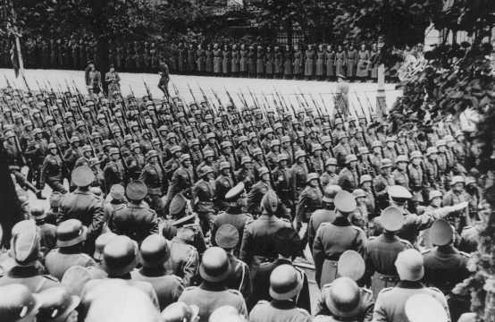 <p>Adolf Hitler (en bas à droite) fait le salut nazi en passant en revue les troupes allemandes victorieuses. Varsovie, Pologne, 5 octobre 1939.</p>