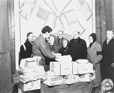 <p>Harry Weinsaft, Joint Distribution Committee representative, gives aid packages to Jewish refugees. Vienna, Austria, postwar.</p>