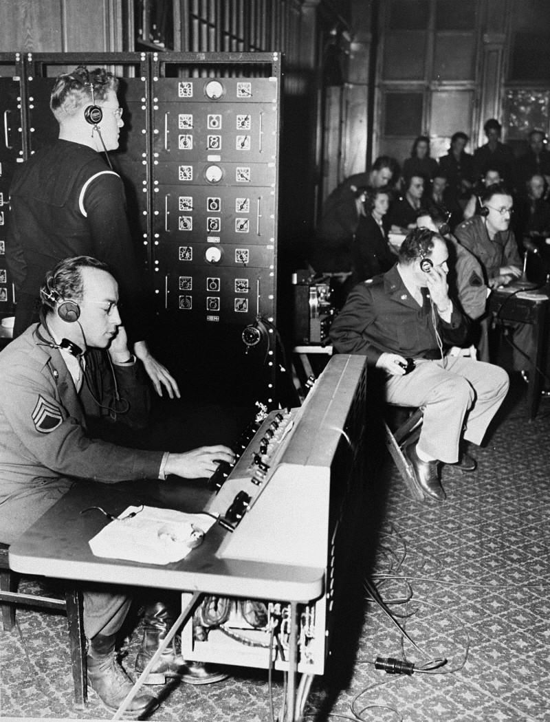 <p>Οι επίσημες γλώσσες στις δίκες της Νυρεμβέργης ήταν τα Αγγλικά, τα Γαλλικά, τα Ρωσικά και τα Γερμανικά. Διερμηνείς παρείχαν ταυτόχρονη διερμηνεία των διαδικασιών. Εδώ, κατευθύνουν τις διερμηνείες μέσω ενός τηλεφωνικού κέντρου στους συμμετέχοντες της δίκης. Νυρεμβέργη, Γερμανία, Νοέμβριος 1945.</p>