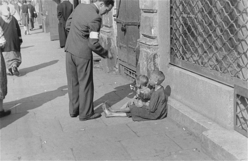 A Warsaw ghetto resident gives money to two children on a Warsaw ghetto street. [LCID: 89467]