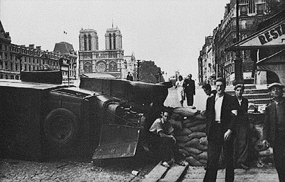 During the battle to liberate the French capital, a barricade is hastily built near the cathedral of Notre Dame.