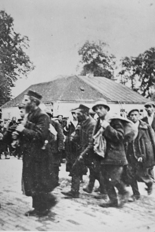 <p>طابور من السجناء يصلون إلى محتشد الإبادة في بيلزيك، بولندا، تقريبًا. 1942.</p>