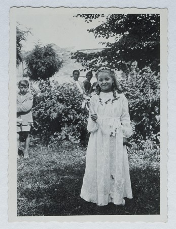 Selma Schwarzwald poses outside while wearing her first communion dress. [LCID: 58258]