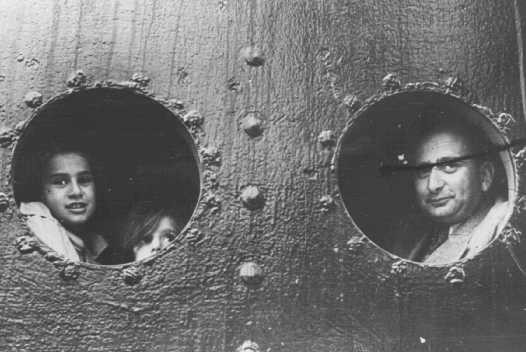 "<p>German Jewish refugees look through portholes of the <a href=""/narrative/4719/en""><em>St. Louis</em></a>, in Havana harbor. Cuba refused to let the passengers disembark. Cuba, May or June, 1939.</p>"