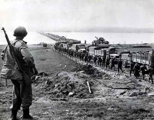 German prisoners file across the Rhine as American supply trucks move forward toward the front. [LCID: sc255]