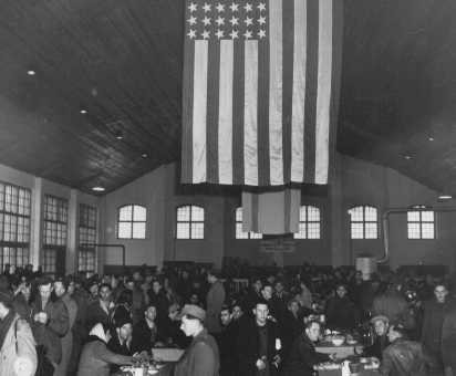 <p>A US flag hangs from the ceiling of the main dining room at the Landsberg displaced persons camp. Germany, December 6, 1945.</p>