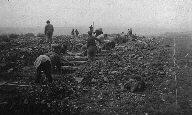German civilians conscripted from nearby towns dig graves for some of the victims of the Ohrdruf camp. [LCID: 10313]
