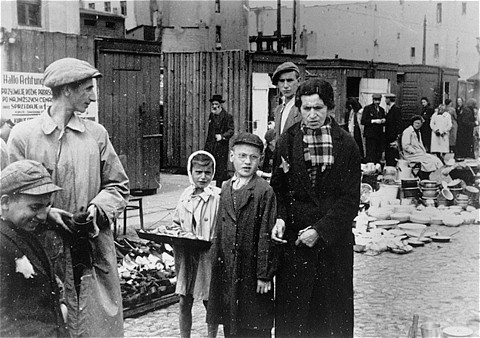 A child vendor among those selling miscellaneous wares at the market in the Lodz ghetto. [LCID: 51128]