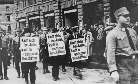 "<p>Three Jewish businessmen are forced to march down a crowded Leipzig street while carrying signs reading: ""Don't buy from Jews. Shop in German businesses!"" Leipzig, Germany, 1935.</p>"