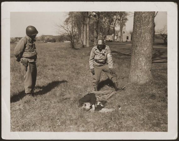 """<p>An American medic and soldier stand by the corpse of a prisoner shot on the road near <a href=""""/narrative/8101"""">Gardelegen</a>. The prisoner was shot by the SS when he was too exhausted to continue on a death march. Germany, April 14-18, 1945.</p>"""