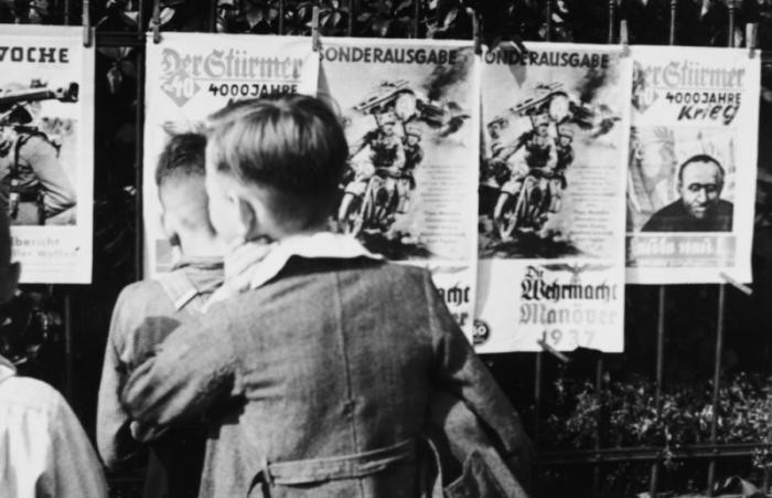 """A group of young German boys view """"Der Stuermer,"""" """"Die Woche,"""" and other propaganda posters that are posted on a fence in Berlin, Germany, 1937."""