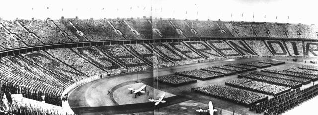 "<p>At a ceremony during the <a href=""/narrative/7139/en"">1936 Olympic Games</a>, German spectators spell out the phrase, directed at Adolf Hitler, ""Wir gehoeren Dir"" [We belong to you]. Berlin, Germany, August 1936.</p>"
