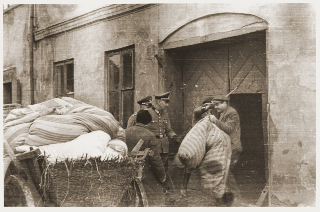"""<p>A member of the German Order Police raises a stick to beat a Jew who is loading his bundles onto a wagon during expulsion from the community of Sieradz in German-occupied <a href=""""/narrative/2103"""">Poland</a>. Photo dated 1940–1942.</p>"""