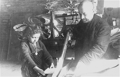 "<p>A Jewish man and child at <a href=""/narrative/3384"">forced labor</a> in a factory in the <a href=""/narrative/2152"">Lodz</a> ghetto. Lodz, Poland, date uncertain.</p>"
