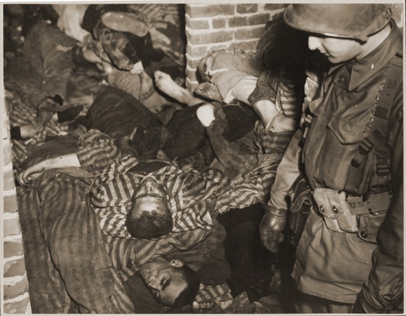 "<p>A US Army soldier views the bodies of prisoners piled on top of one another in the doorway of a barracks in <a href=""/narrative/7988"">Wöbbelin</a>. Germany, May 4–5, 1945.</p>"
