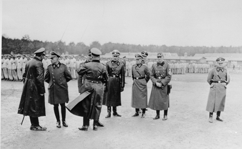 <p>Members of the SS and police speak among themselves during a roll call at the Buchenwald concentration camp. Buchenwald, Germany, 1938-1940.</p>