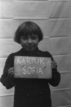 "<p class=""document-desc moreless"">Sofia Karpuk holds a name card intended to help any of her surviving family members locate her at the <a href=""/narrative/35450"">Kloster Indersdorf</a> displaced persons camp. This photograph was published in newspapers to facilitate reuniting the family. Kloster Indersdorf, Germany, October-November 1945. </p>