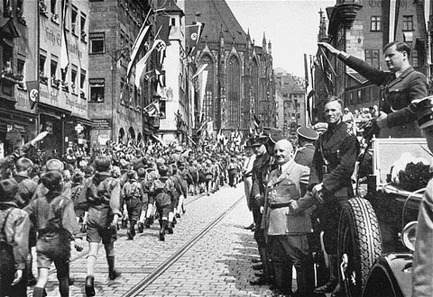 Members of the Hitler Youth march before their leader, Baldur von Schirach (at right, saluting), and other Nazi officials including ... [LCID: 08063]